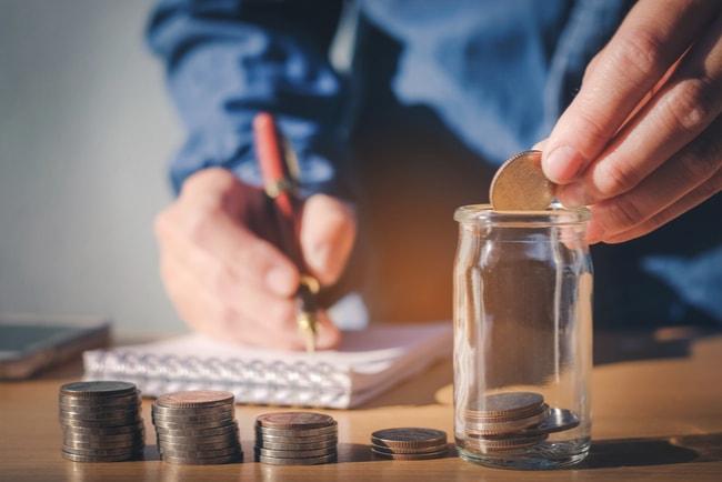 En man som stoppar ner mynt i en glasbruk och gör noteringar i ett pappersblock