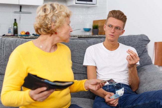 Äldre kvinna ger pengar till sitt barnbarn