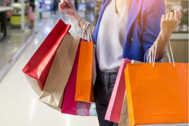 Kvinna i ett shoppingcentrum bär på flera olika kassar i olika färger.