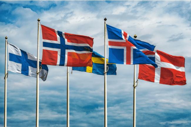 Nordens alla flaggor vajar i vinden mot en blå himmel med några vita moln