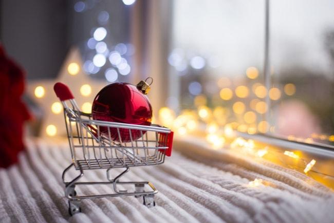 röd julgranskula i miniatyrkundvagn i skyltfönster