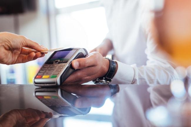 Hand som håller fram ett betalkort mot en betalterminal för att betala ett köp.