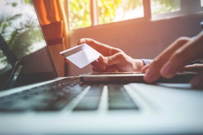 man håller kreditkort och ska betala över nätet via laptop