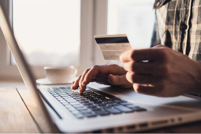 man håller kreditkort och sitter vid dator