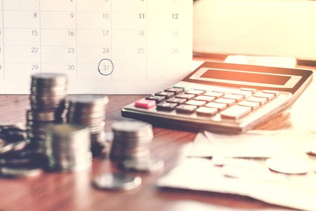 Mynt, miniräknare, lite papper och en kalender i bakgrunden på ett bord.