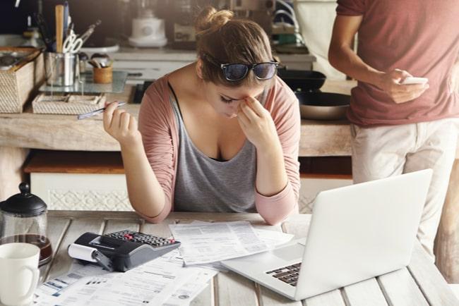 Deprimerad kvinna sitter med laptop och ska betala räkningarna.